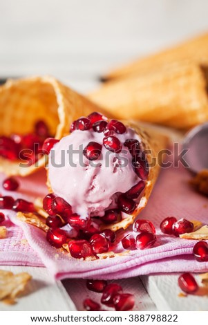 Ice cream in a waffle cone with pomegranate seeds