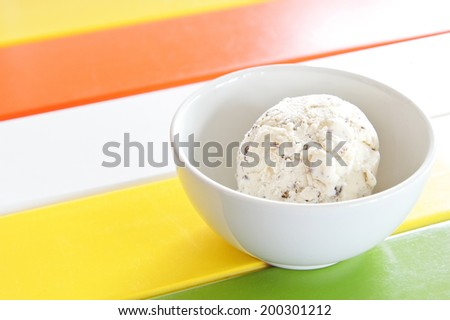 Ice cream in white bowl and on color table.