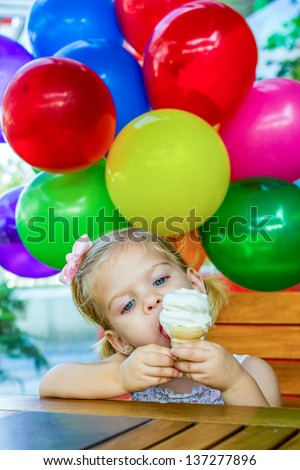 Ice Cream. Little girl eating an ice cream with balloons at the background - stock photo