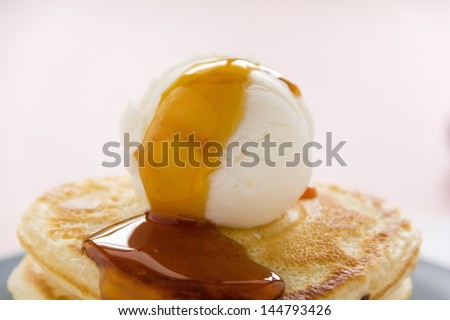 Ice cream on pancakes with golden maple syrup ready to serve. - stock photo