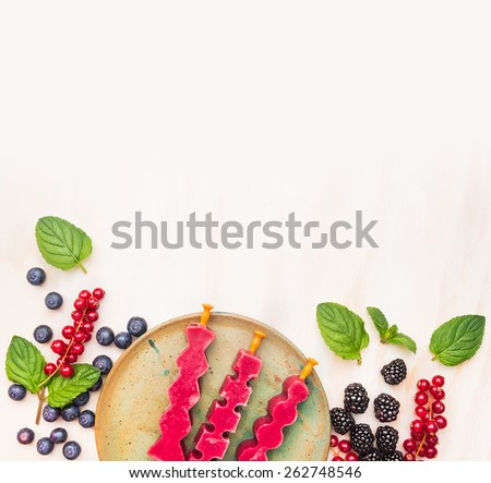 Ice cream pops in plate with summer berries:  red currant, blackberries, blueberries and peppermint leaves on white wooden background, top view place for text, frame - stock photo
