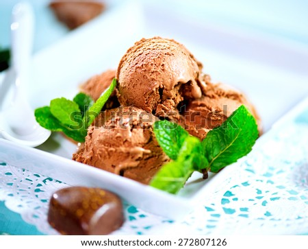 Ice cream scoops with chocolate topping. Brown chocolate icecream served with dark chocolate topping and mint - stock photo