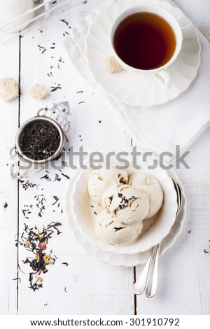 Ice cream with Earl grey tea flavor in white ceramic bowl on a white wooden background - stock photo
