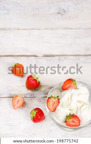 ice cream with strawberry on a white wood background. toning.selective focus on the left strawberry on the ice cream - stock photo