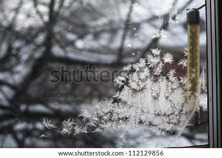 Ice crystals on window during winter with thermometer