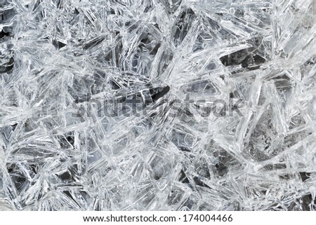 ice crystals over frozen puddle in spring forest  - stock photo