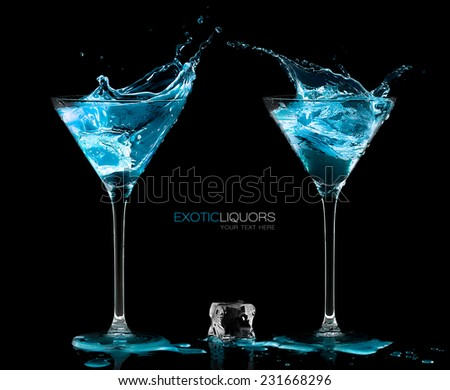 Ice cube between two cocktail glasses filled with blue alcoholic exotic liqueur splashing out, with copy space on black, concept of style and celebration. Template design with sample text - stock photo