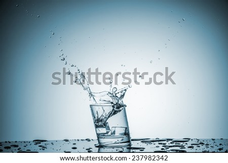 ice cube falling into a glass of water on blue background - stock photo