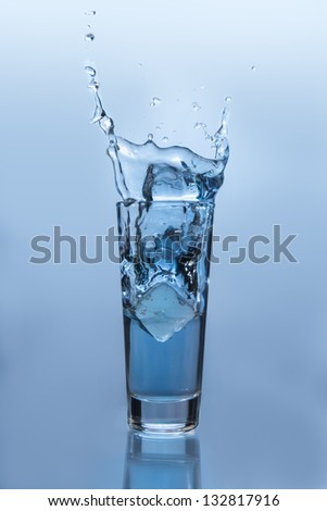 Ice cube falling into glass of water on blue background