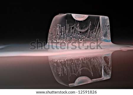 Ice cube on a reflecting surface - stock photo