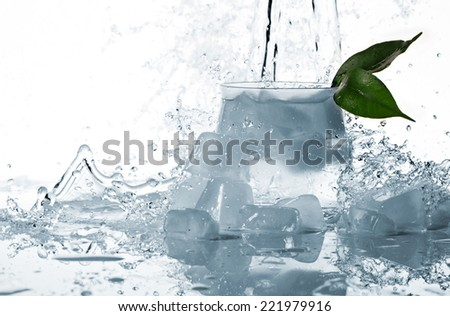 ice cubes and green leaf in glass, and splashes of water on white background - stock photo