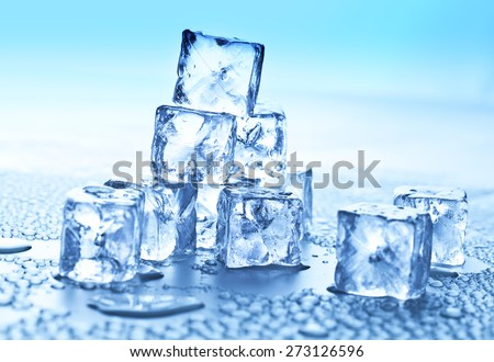 ice cubes and water drops on blue background - stock photo