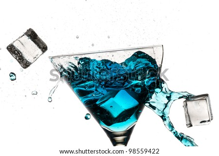 Ice cubes breaking martini glass filled with blue liqueur on white background - stock photo