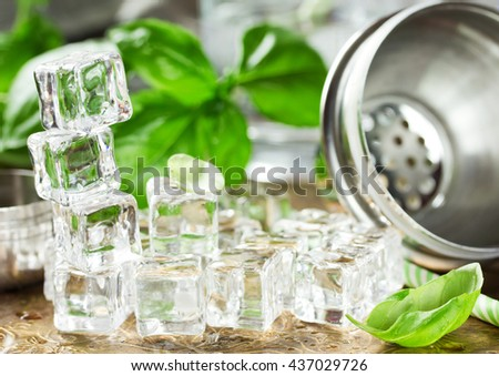 Ice cubes, fresh basil, shaker to prepare refreshing drink in bar - stock photo