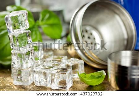 Ice cubes, fresh basil, shaker to prepare refreshing drink in bar - stock photo