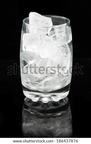ice cubes in a glass cup on black background.
