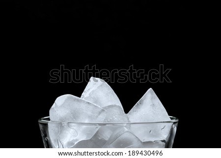 Ice cubes in a glass, over black background