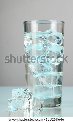 Ice cubes in glass on light blue background