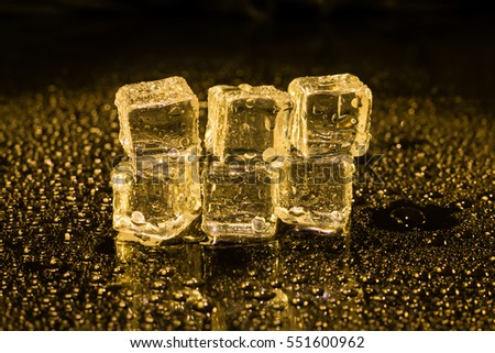 Ice cubes in yellow light on black wet table.
