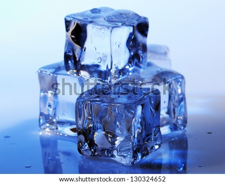 Ice cubes on a blue background. - stock photo