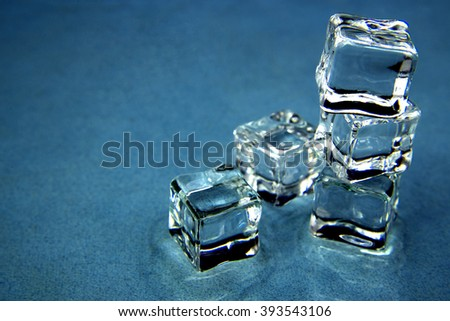 Ice cubes over blue background. - stock photo