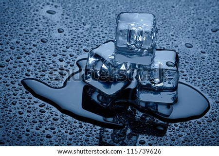 Ice cubes over dark background - stock photo