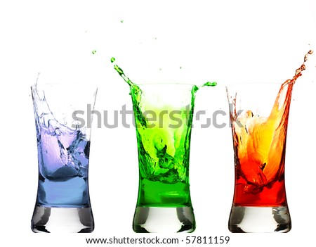 ice cubes thrown in some glasses with drinks - stock photo
