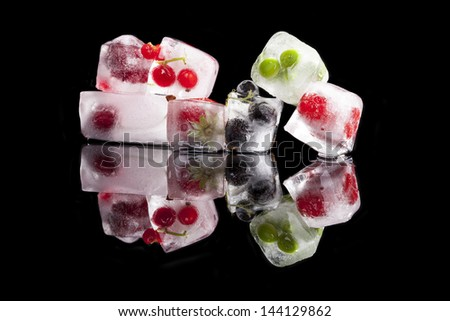 Ice cubes with fruit and vegetable isolated on black background with reflection. Cherry, green peas, blackcurrant and raspberries frozen in ice cubes. Fresh healthy summer eating.  - stock photo