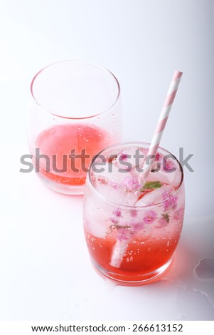 Ice cubes with pink flowers in glass  with paper straw on white background - stock photo
