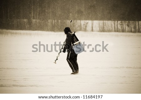 ice fishing in the north of Sweden on a cold and snowy day - stock photo
