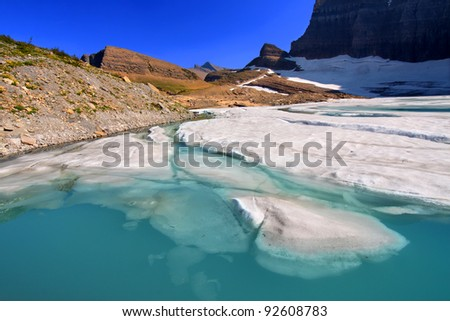 Ice floats in a pond by the Grinnell Glacier in Glacier National Park of Montana - stock photo