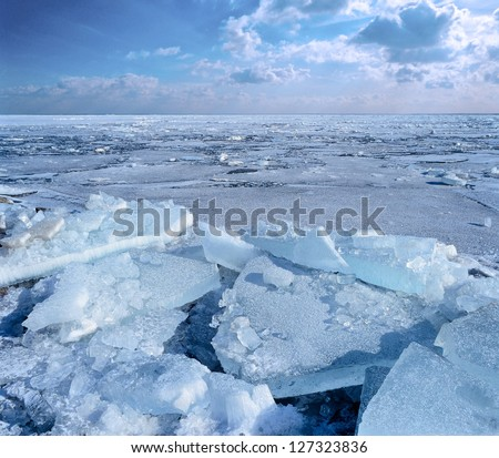 Ice floe breaking up against shore with sea ice during freezing winter weather. Fast ice. - stock photo