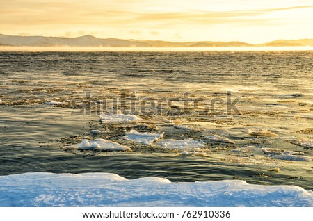 Ice floes floating on the fog water in the lake Baikal. Sunset