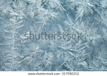 Ice flowers macro view. Frost flowers ornamental pattern. Window frost. Winter in the window. Frozen window. - stock photo