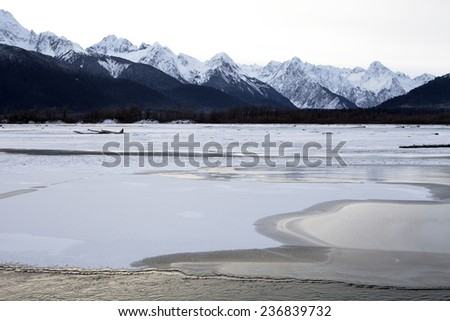 Ice forming on the Chilkat river near Haines Alaska in early winter with snow covered mountains in the background in evening light. - stock photo