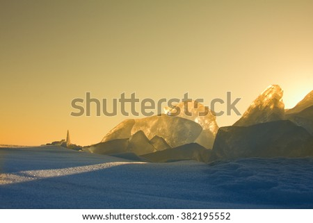 Ice glows and shines against backdrop of sunsets. Back shooting snow and ice