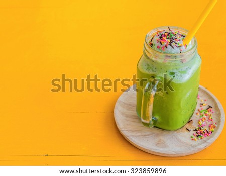 Ice Green tea with sugar roll  smoothies on wooden plate yellow background. - stock photo