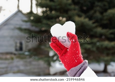 ice heart in a red glove - stock photo