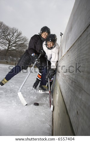 Ice hockey player boy slamming other player into wall trying to get to puck. - stock photo