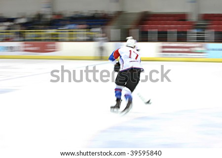 Ice hockey player in motion on the ice - stock photo