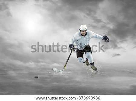 Ice hockey player on the ice under sky - stock photo