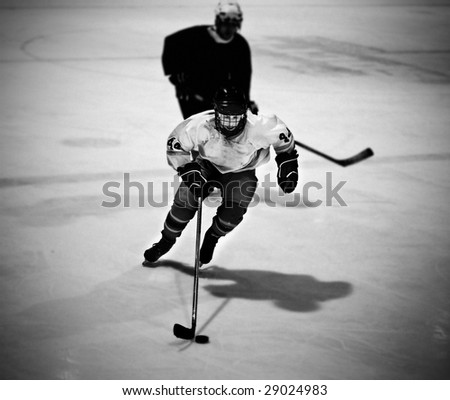 Ice hockey player skating with the puck - stock photo