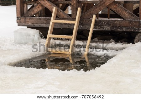 Ice-hole with wooden stairs on the frozen lake