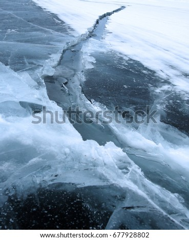 Ice hummocks on the northern shore of Olkhon Island on Lake Baikal. Fresh crack broke the thick ice. Fresh clean water rises from the depths and freeze in the cold. Ice Storm. Photo partially tinted
