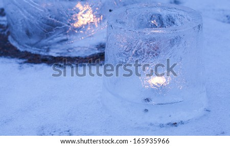 ice lanterns - lanterns made of ice from partially frozed water containers, candle inside, set outside in evening light