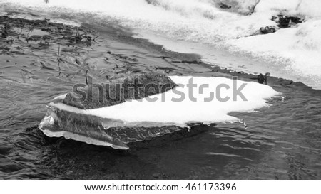 ice of interesting shape on the stones in the river in black and white