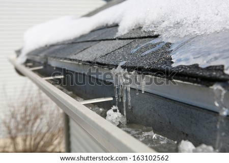 Ice on roof and gutters - stock photo