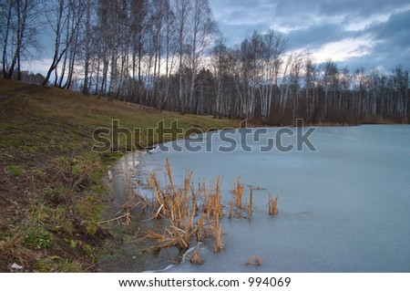 Ice on the forest pond - stock photo