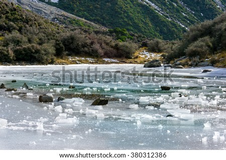 Ice pieces of frozen lake against wintry mountain background. Blue lakes, South Island, New Zealand. Stunning icy scenery landscape - stock photo