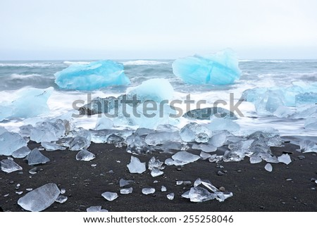 Ice rocks on a black sand beach in Iceland - stock photo